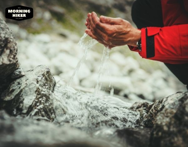 man drinking water from a river